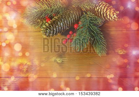 christmas decoration, holidays, new year and decor concept - close up of natural fir branch and fir-cone on wooden table over lights