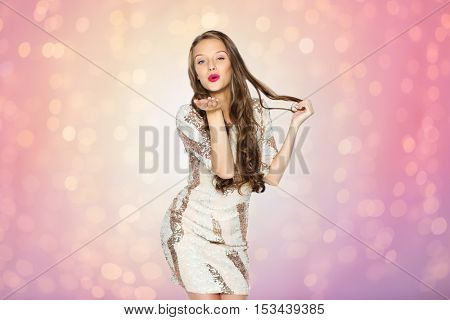 people, style, holidays, hairstyle and fashion concept - happy young woman or teen girl in fancy dress with sequins and long wavy hair sending blow kiss over rose quartz and serenity lights background