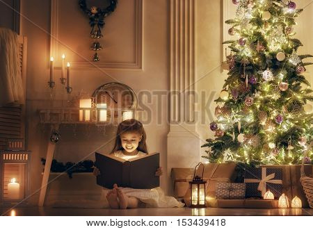 Merry Christmas and Happy Holidays! Cheerful cute little child girl with magic book. Kid reads a fairy tale near Christmas tree indoors.