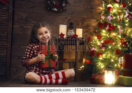 Merry Christmas and Happy Holidays! Cheerful cute child girl with present. Kid holds a gift box near Christmas tree indoors.
