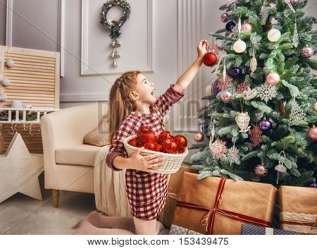 Merry Christmas and Happy Holidays!  Cute little child girl is decorating the Christmas tree indoors.