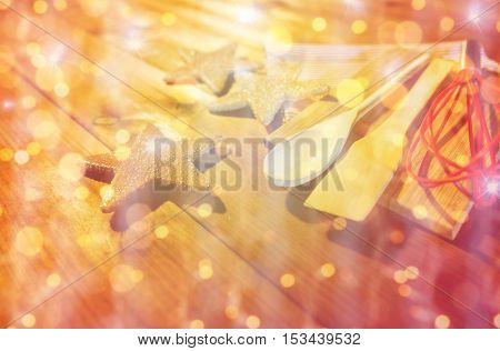 baking, cooking, christmas and holidays concept - close up of gingerbread cookies, kitchenware set and towel on wooden cutting board over lights