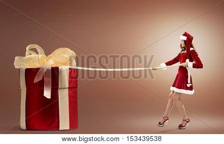 Santa woman pulling huge red gift box