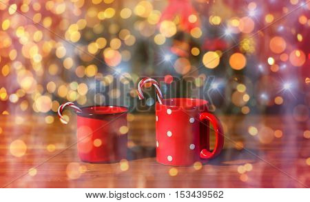 holidays, christmas, winter, food and drinks concept - close up of candy canes in cups on wooden table over lights