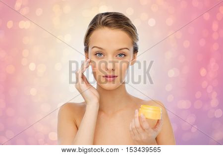 beauty, people, cosmetics, skincare and cosmetics concept - young woman applying cream to her face over rose quartz and serenity lights background