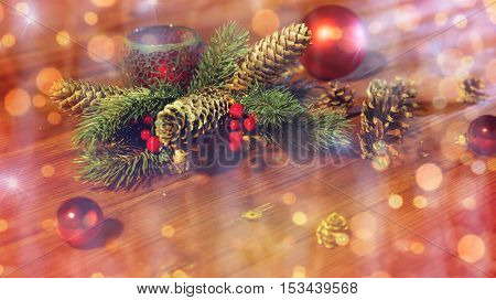 christmas, decoration, holidays and new year concept - close up of natural fir branch decoration with fir-cones, balls and candle in lantern on wooden table over lights