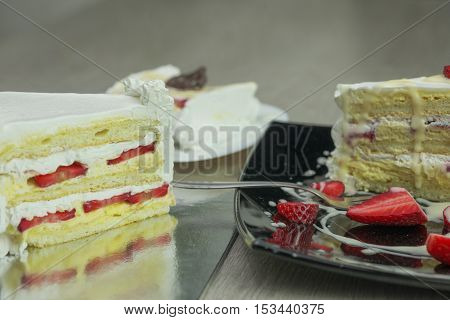 Delicious slice of cake with strawberries and fruit shallow depth of field