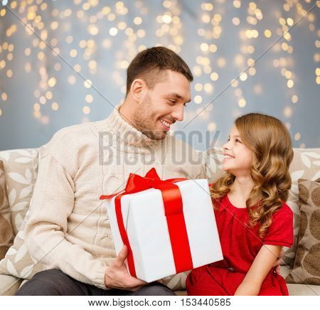 family, christmas, holidays and people concept - smiling father and daughter with gift box looking at each other over lights background