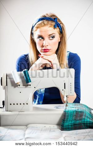 Woman sews and thinking about next cut
