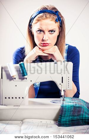 Woman sews and getting tired of work