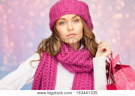 winter holidays, sale, christmas and people concept - beautiful young woman in hat and mittens with shopping bags over rose quartz and serenity lights background