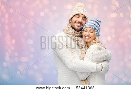 winter, holidays, couple, christmas and people concept - smiling man and woman in hats and scarf hugging over rose quartz and serenity lights background