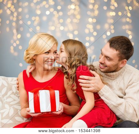 holidays, family and people concept - happy girl kissing her mother with christmas gift over lights background