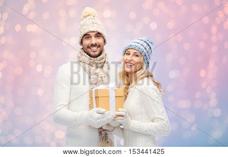 winter, holidays, couple, christmas and people concept - smiling man and woman in hats and scarf with gift box over rose quartz and serenity lights background