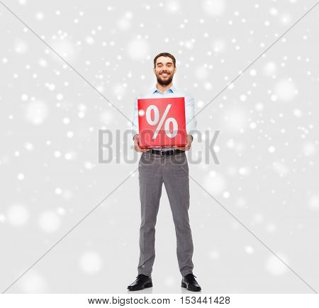 people, sale, shopping, christmas and winter holidays concept - smiling man holding red percentage sign over snow background
