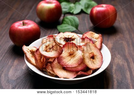 Fruit snack dehydrated apple chips in bowl on wooden table