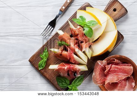 Fresh melon with prosciutto and basil. Antipasti. Top view on wooden table with copy space for your text