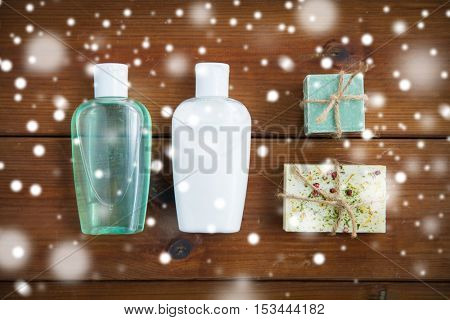 beauty, spa, bodycare, bath and natural cosmetics concept - handmade soap bars and lotion bottles on wooden table over snow