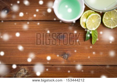 beauty, spa, bodycare and natural cosmetics concept - f bowls with citrus body lotion, cream and limes on wooden table over snow