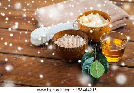 beauty, spa, bodycare, natural cosmetics and bath concept - himalayan pink salt and body scrub with brush and glass of honey on wooden table over snow