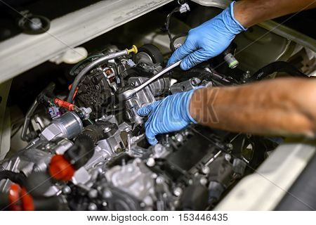 Hands of a mechanic wearing blue gloves working on a car engine with a spanner in a concept of maintenance and repair