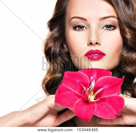 Portrait of young beautiful adult girl with bright red lips and flower near the face - isolated on white background
