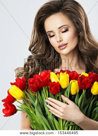 Portrait of calm beautiful young woman with flowers. Attractive girl with long brown hairs