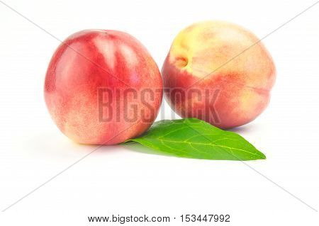 Ripe juicy nectarines with green leaves isolated on white background.