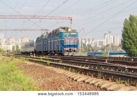 Passenger inter-city train with electric locomotive on the background of urban development in autumn day