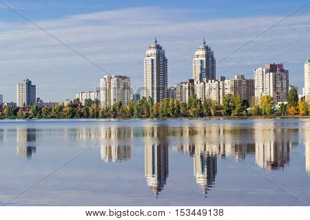 Modern housing estate on the banks of the bay of the river and building reflecting in the water in autumn morning