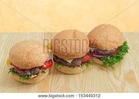 Three hamburgers with beef patty cheese vegetables and condiments on a light wooden surface