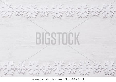 Christmas soft snowflakes on a wood white background. New Year frame background.