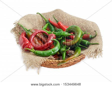 Pile of a red and green peppers chili on a sackcloth in a small wicker basket on a light background