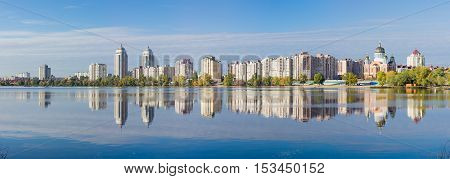 Panorama of modern housing estate on the banks of the bay of the river and building reflecting in the water in autumn morning