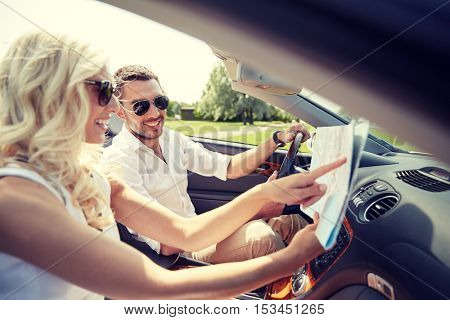 road trip, travel, summer vacation and people concept - happy man and woman driving in cabriolet car with map