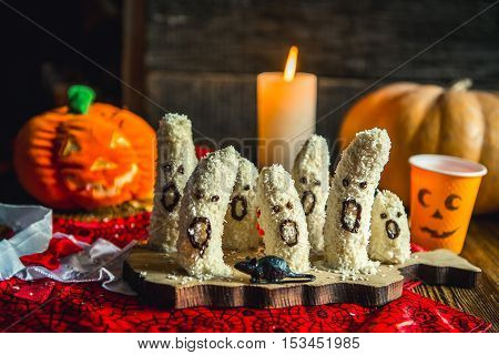 Homemade halloween scary banana ghosts monsters with chocolate faces. funny dessert recipe for party decoration fruits on vintage wooden table background and red fabric.