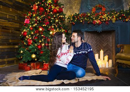 Young couple near fireplace celebrating Christmas. Love and relationship concept.