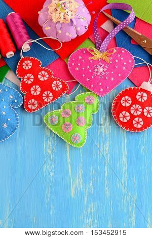 Christmas tree crafts, thread set, scissors, needle, colorful felt sheets, pincushion, pins on blue wooden background with empty place for text. Sewing concept. Christmas background