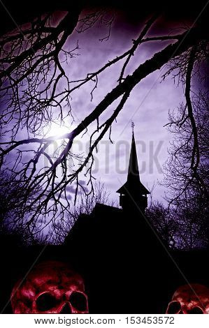 Creepy Halloween background with a silhouette of a church and skull in Transylvania