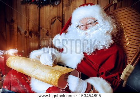 Kind Santa Claus sits in his wooden house and writes something on a scroll. Santa's mail, wish list.