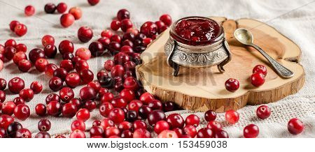 The red berries. Cranberry. Jam from cranberries in a vintage jar. Silverware. Spoon. A wooden Board. Light linen tablecloth.