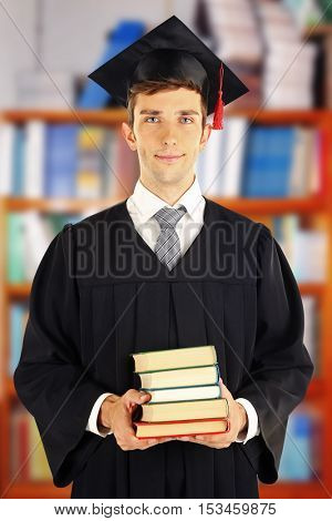 Yong man in graduation gown and cap with stack of books on blurred school library background.