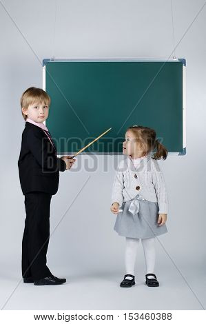 photo of funny boy teaching younger sister