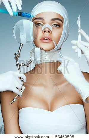 Beauty victim wrapped in medical bandages while doctors with syringes scalpels and magnifying glass near her face. Beauty concept