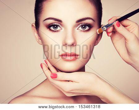 Makeup artist applies skintone. Beautiful woman face. Perfect makeup. Skincare foundation