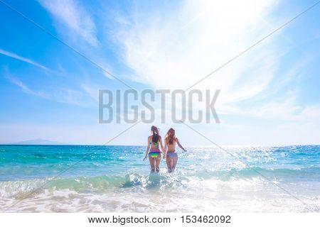 Beautiful fit women in bikni run to tropical sea
