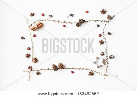 Christmas composition. Larch branches cinnamon sticks anise star dried cranberry. Christmas frame. Flat lay top view