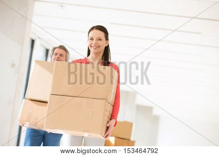 Smiling businesswoman with male colleague carrying cardboard boxes in new office