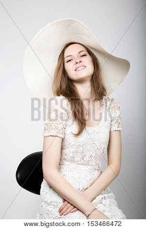 Beautiful young woman wearing a white dress and high heels, sitting on a chair