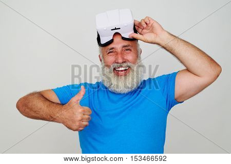 Smiling bearded man is delighted by the work of virtual reality glasses showing thumbs up gesture